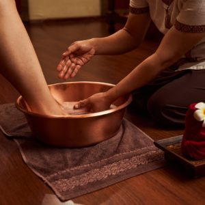 Professional podiatrist preparing client feet for pedicure